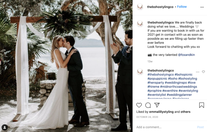 couple getting married under a rustic wedding arch
